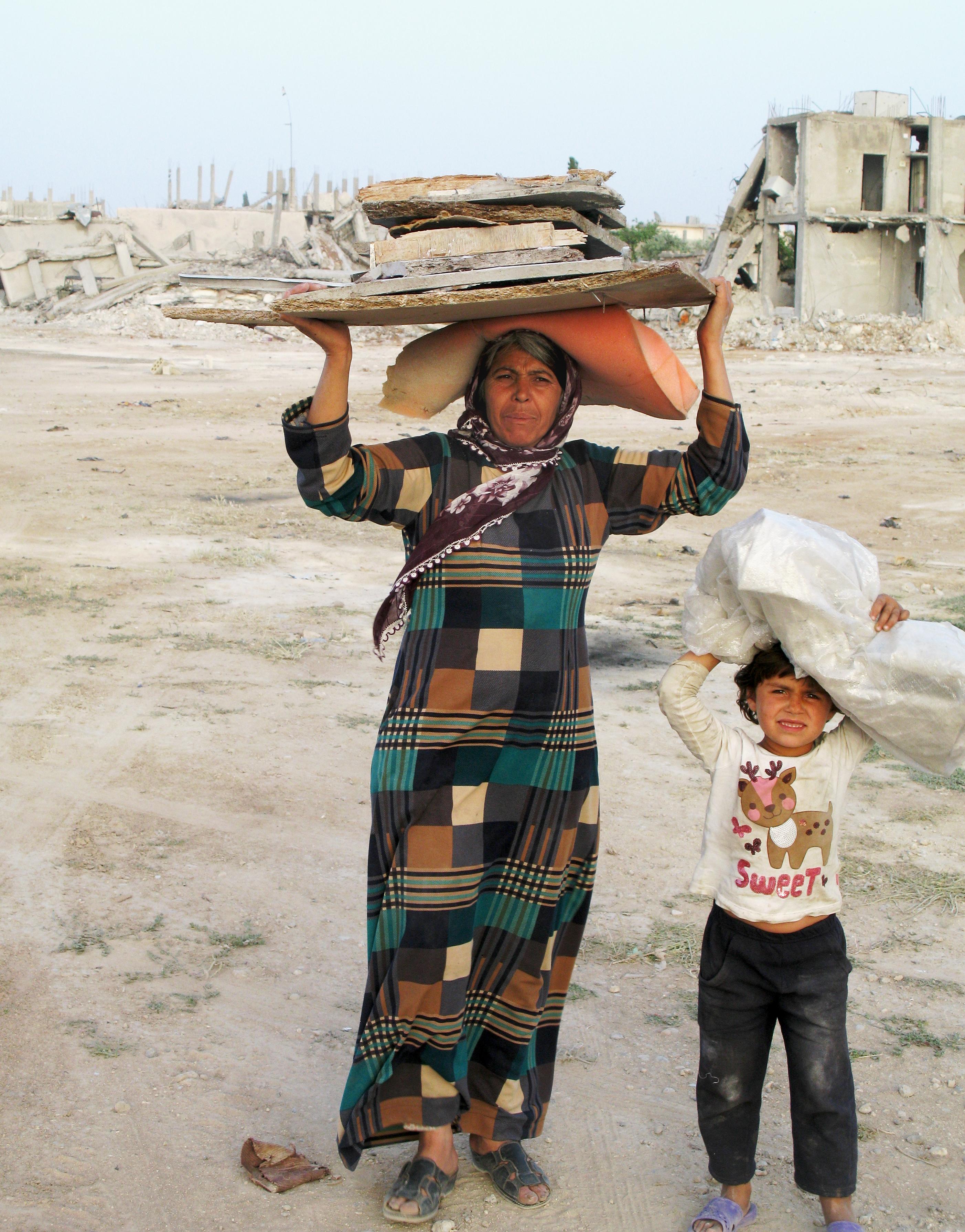 Mor og dotter har henta «byggematerialar» i ruinane. Dei skal heim for å reparere det som før var ei leilighet.