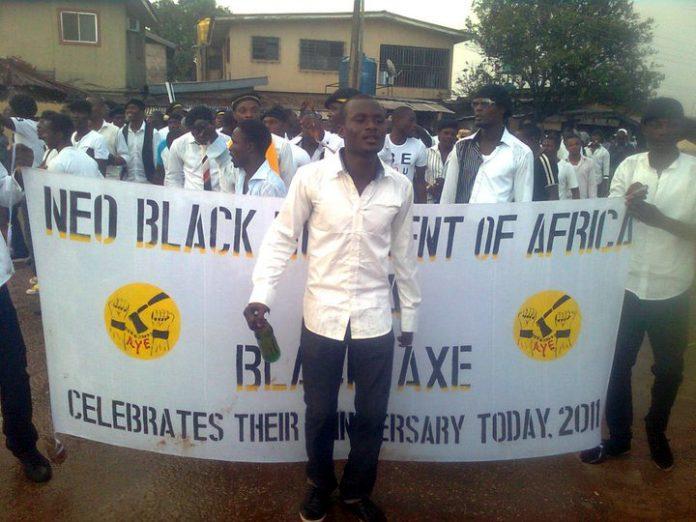 Neo Black Movement of Africa (NBM) benekter en kobling til Black Axe. Her viser de seg fram med et felles banner. (Foto: Wikimedia)